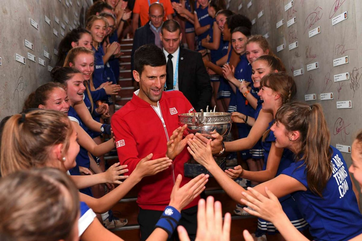 Novak Djokovic celebrates with ball girls after winning the French Open men's singles final match, on June 5, 2016.