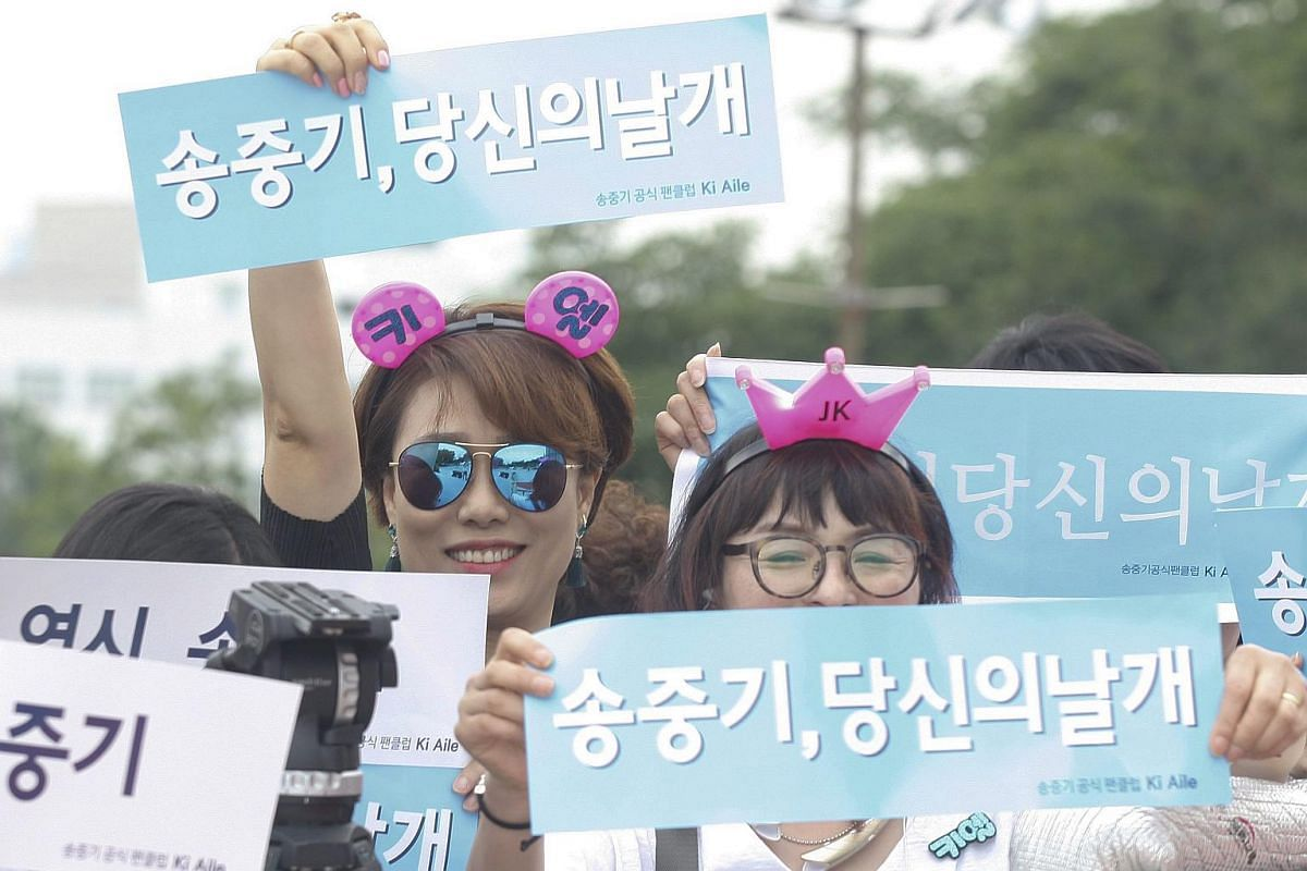 A fan of actor Song Joong-Ki holds up banners reading in Korean 'Your wings Song Joong-Ki' as they wait for the actor's arrival at the 52nd annual Baeksang Art Awards at the Kyunghee University in Seoul, South Korea, on June 3.