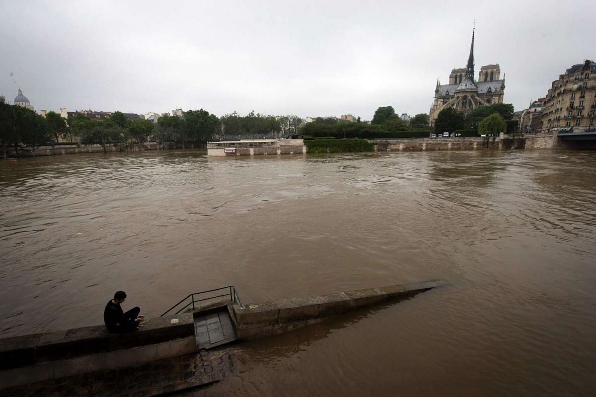 A man sits on a low wall by the rain-swollen river Seine and Notre Dame De Paris cathedral on June 5 in Paris.