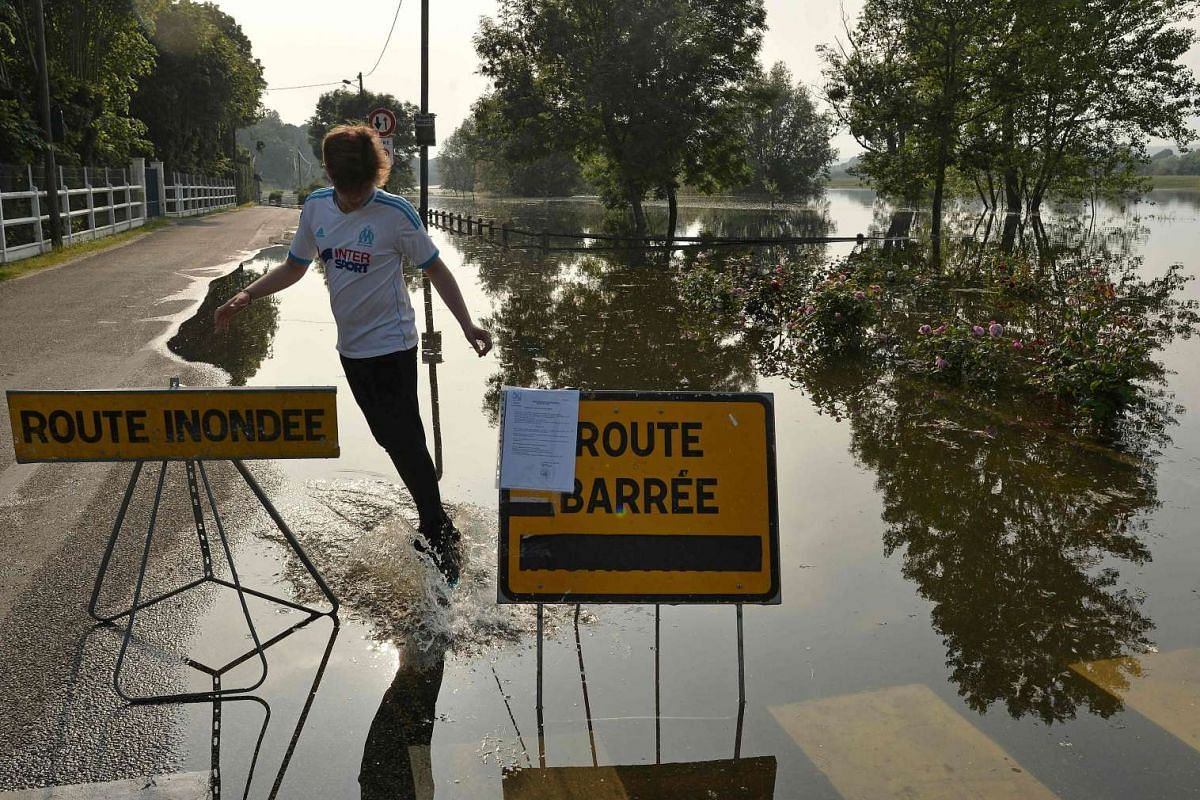 A man skateboards on the edge of a flooded road in Les Damps, western France, on June 5.