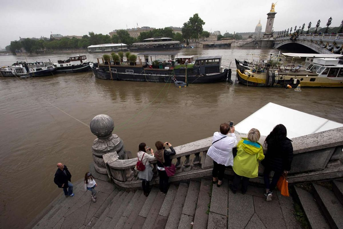 People take pictures of the rain-swollen river Seine on June 5 in Paris.