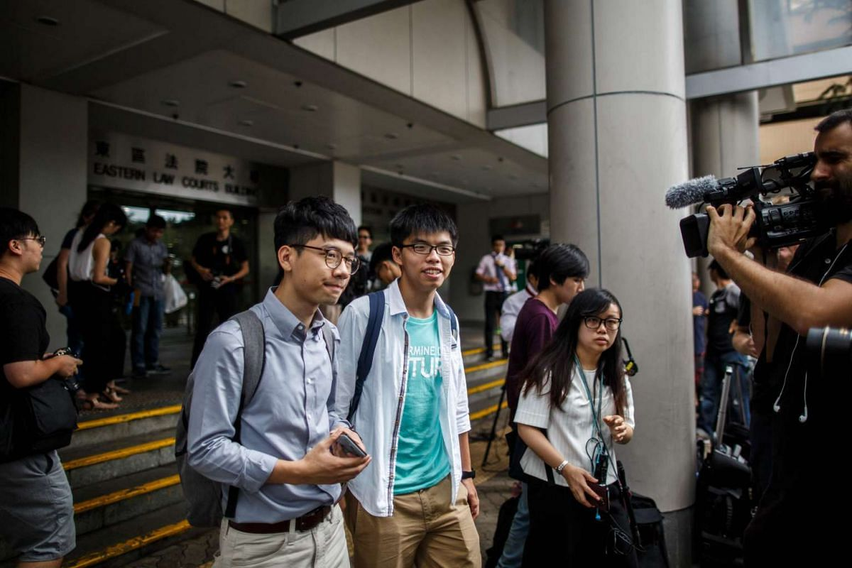 Hong Kong student leader Joshua Wong (centre) and fellow activist Nathan Law leave the Eastern Law Court after being acquitted over an anti-China protest in the first of a raft of cases against him to reach a verdict, in Hong Kong, on June 7, 2016.
