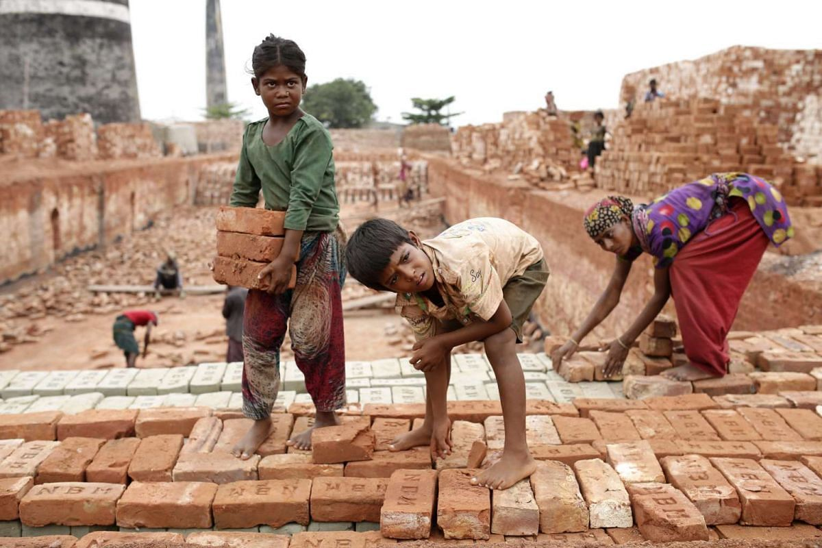 A boy, 8, and a girl, 11, carry bricks as they work along with his father and mother in Dhaka, Bangladesh, on June 1, 2016. The children can earn less than 3 euros if they carry 1,000 bricks.