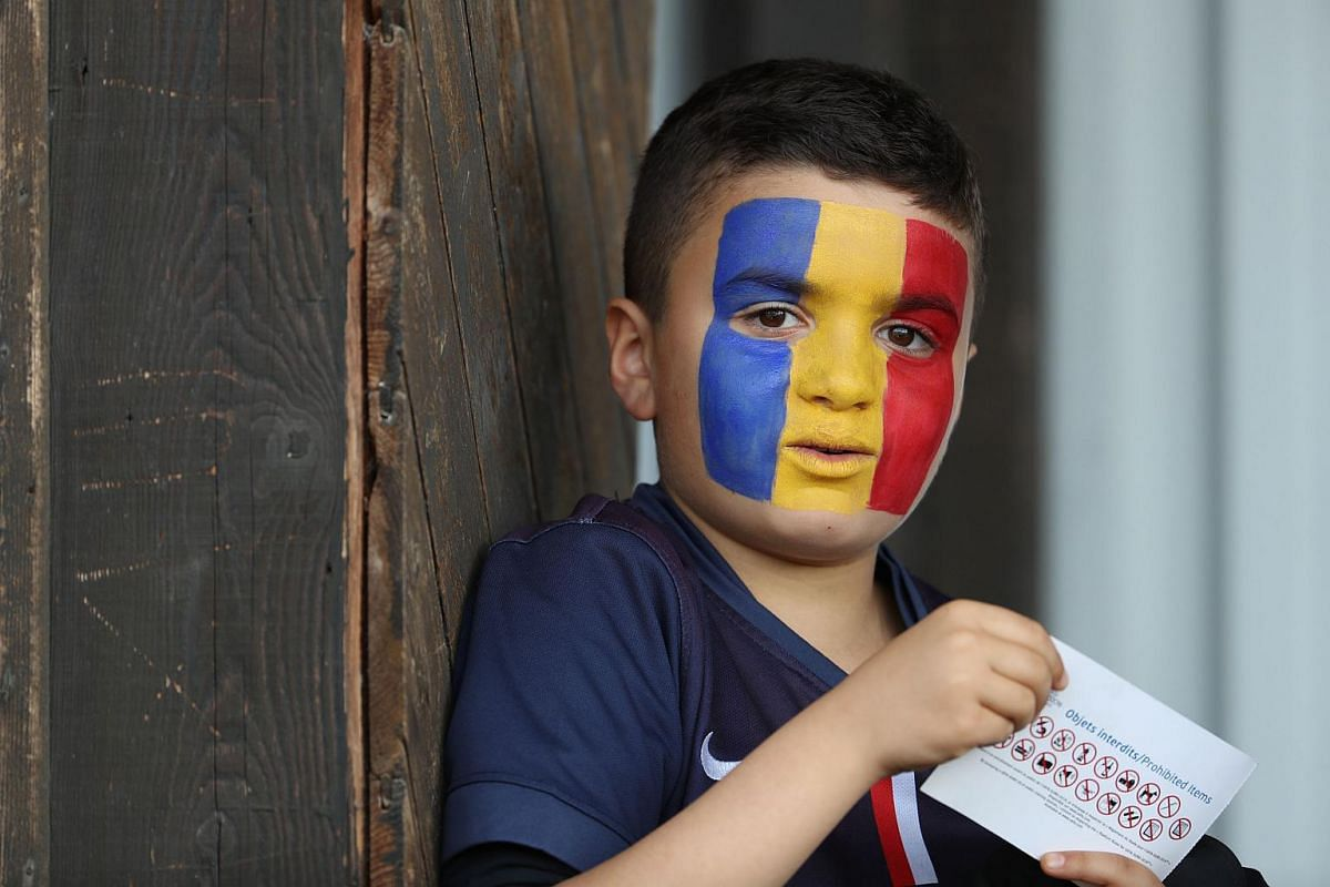 A young fan, with his face painted in the colours of the Romanian flag, attending a Romania training session in Orry-la-Ville on June 5, 2016.
