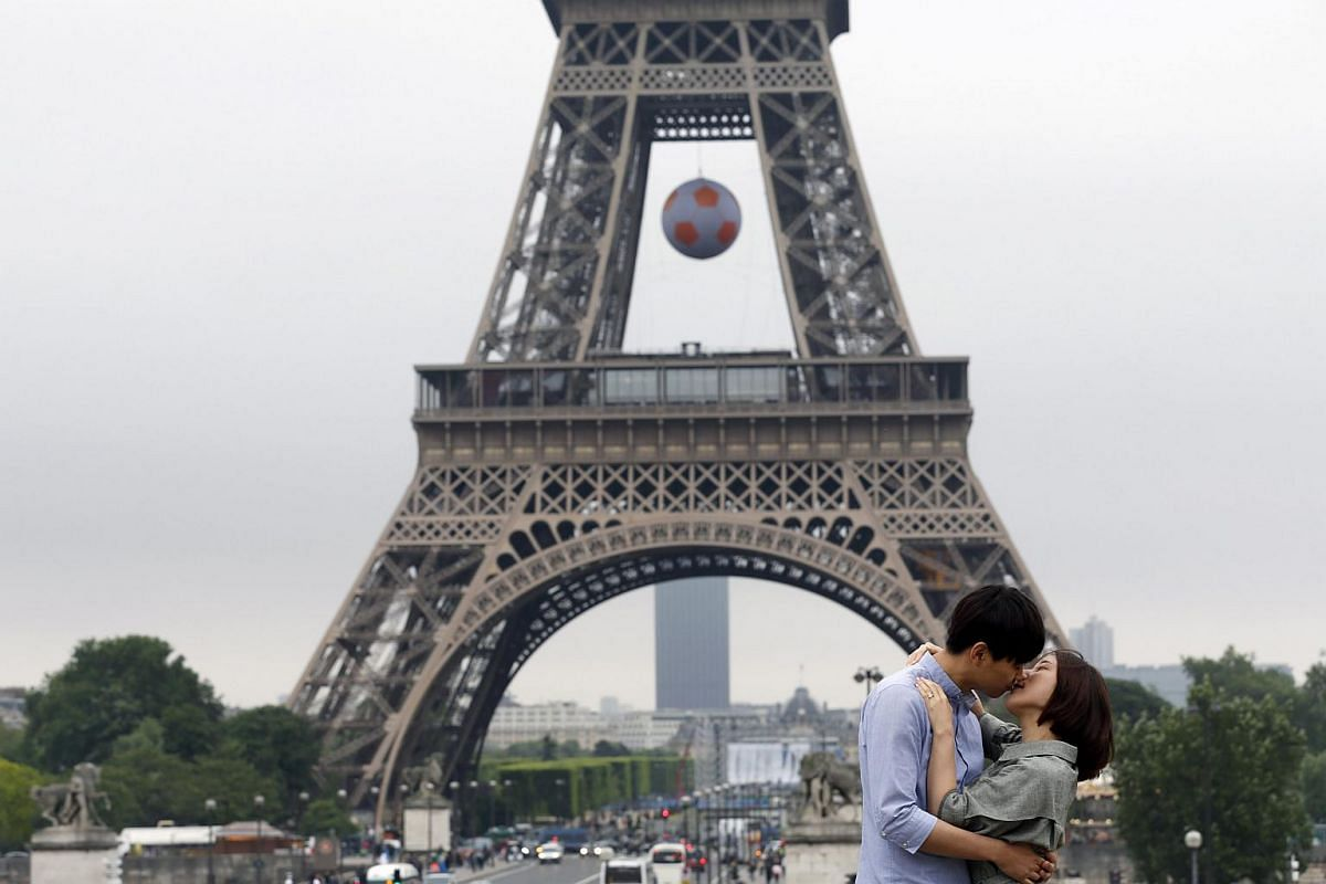 A couple hugging next to the Eiffel Tower, which was decorated with a giant ball for Euro 2016, in Paris on June 2, 2016.