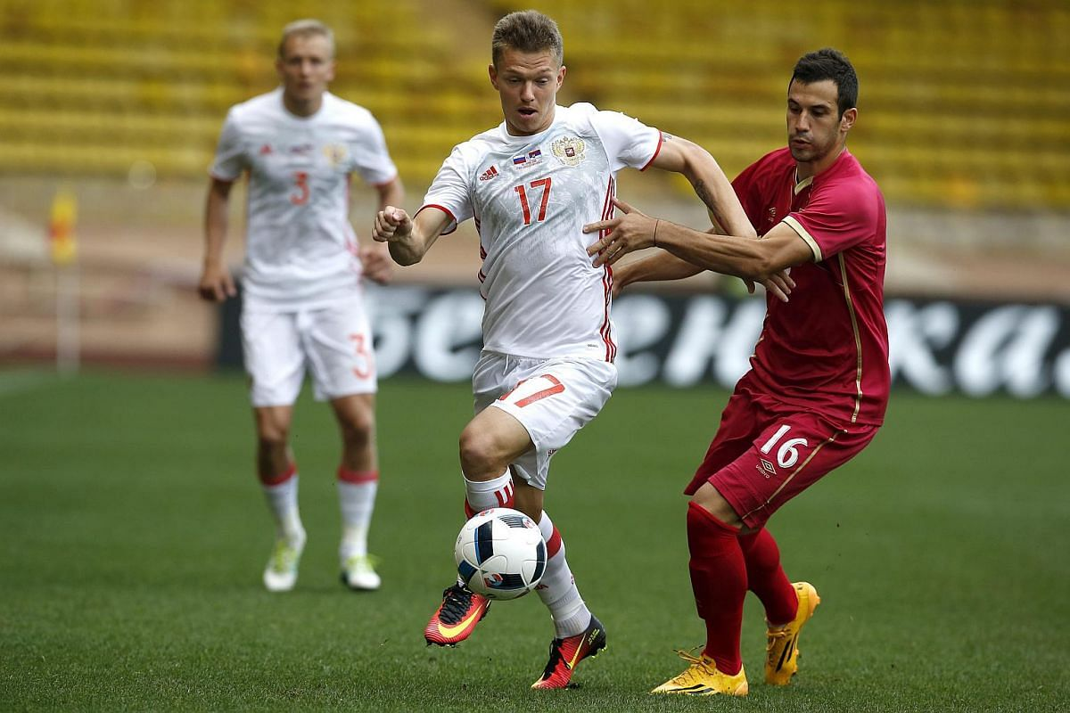 Sebia's Luka Milivojevic (right) vying for the ball with Russia's Oleg Shatov during a friendly match at Louis II stadium in Monaco, on June 5, 2016.