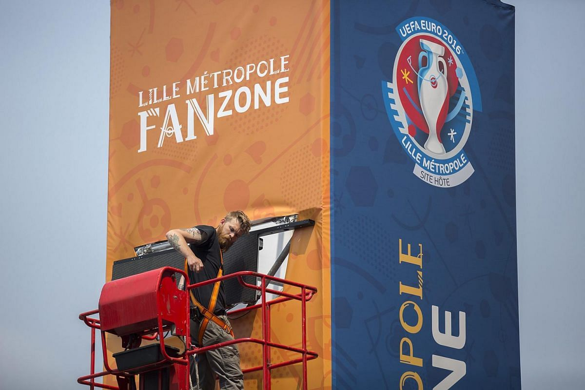 A workman attaching a monitor on a Uefa Euro 2016 fan zone sign in Lille, France, on June 5, 2016.