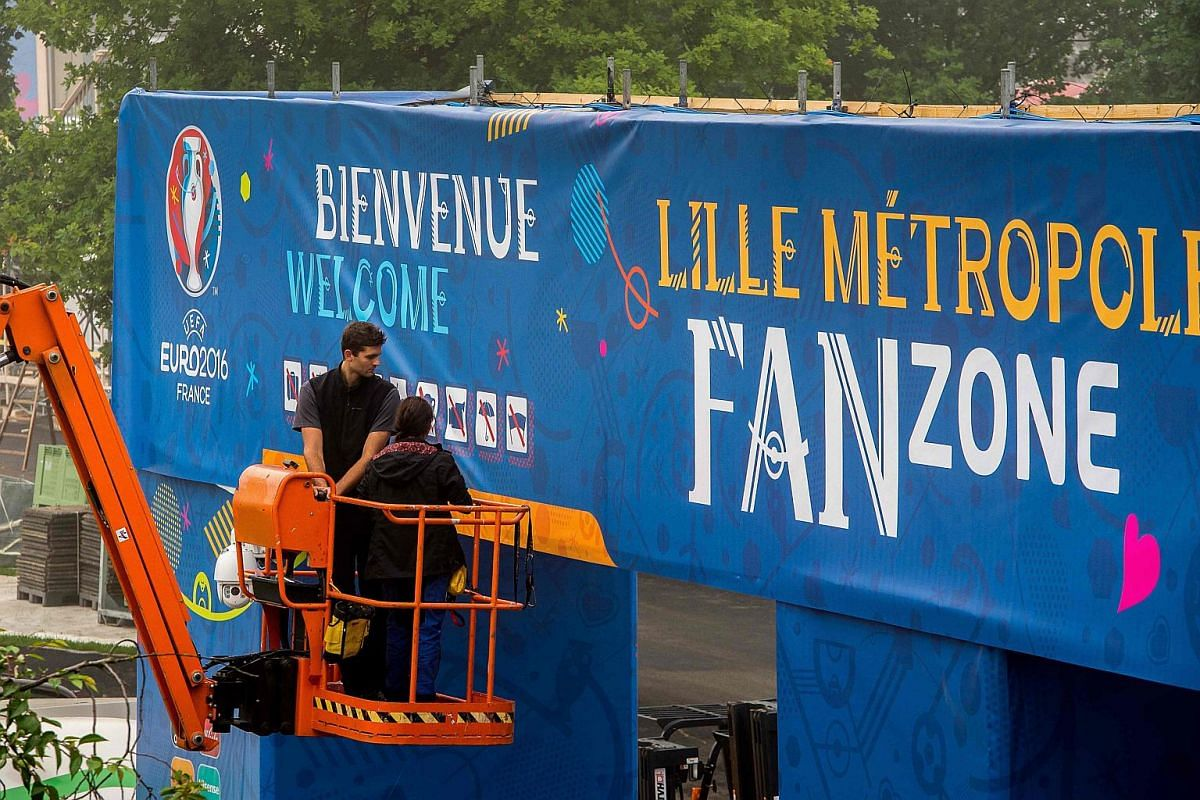 Workers putting up banners and equipment in the fan zone in Lille, northern France, before Euro 2016.