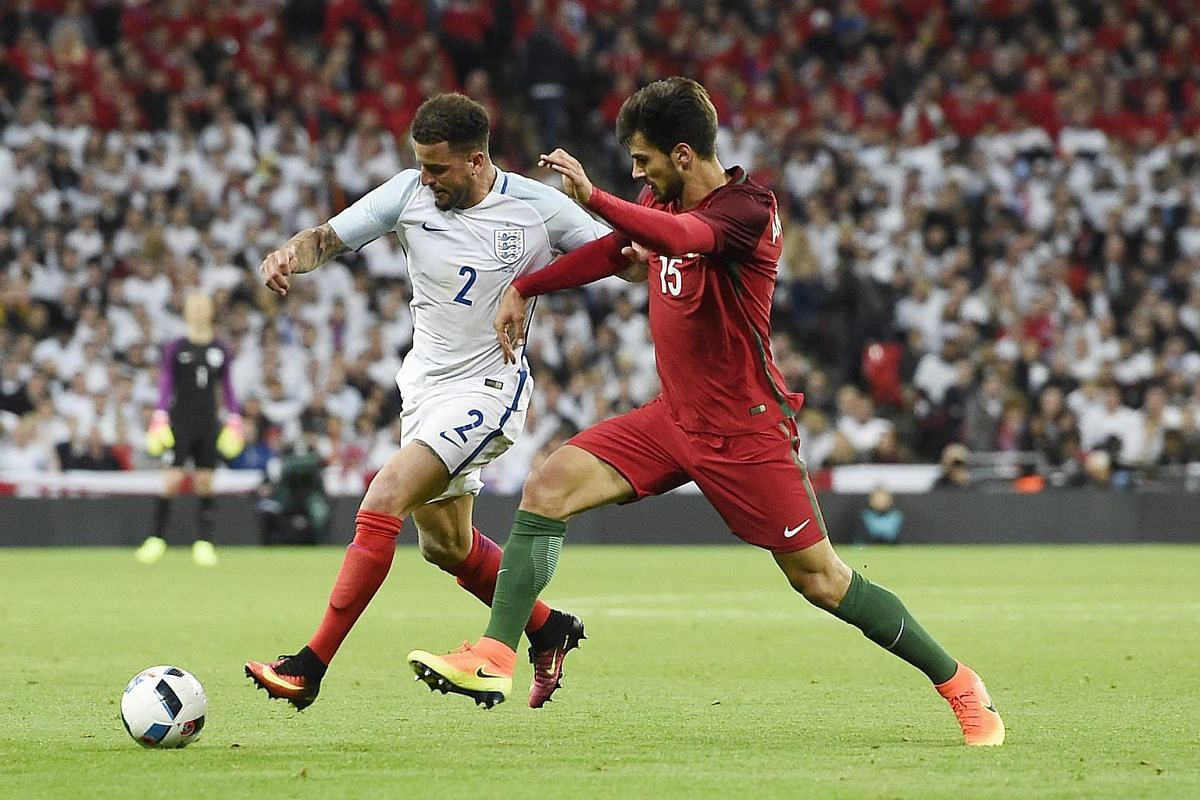 England's Kyle Walker (left) vying for the ball against Portugal's Andre Gomes a friendly match at Wembley in London on June 2, 2016.