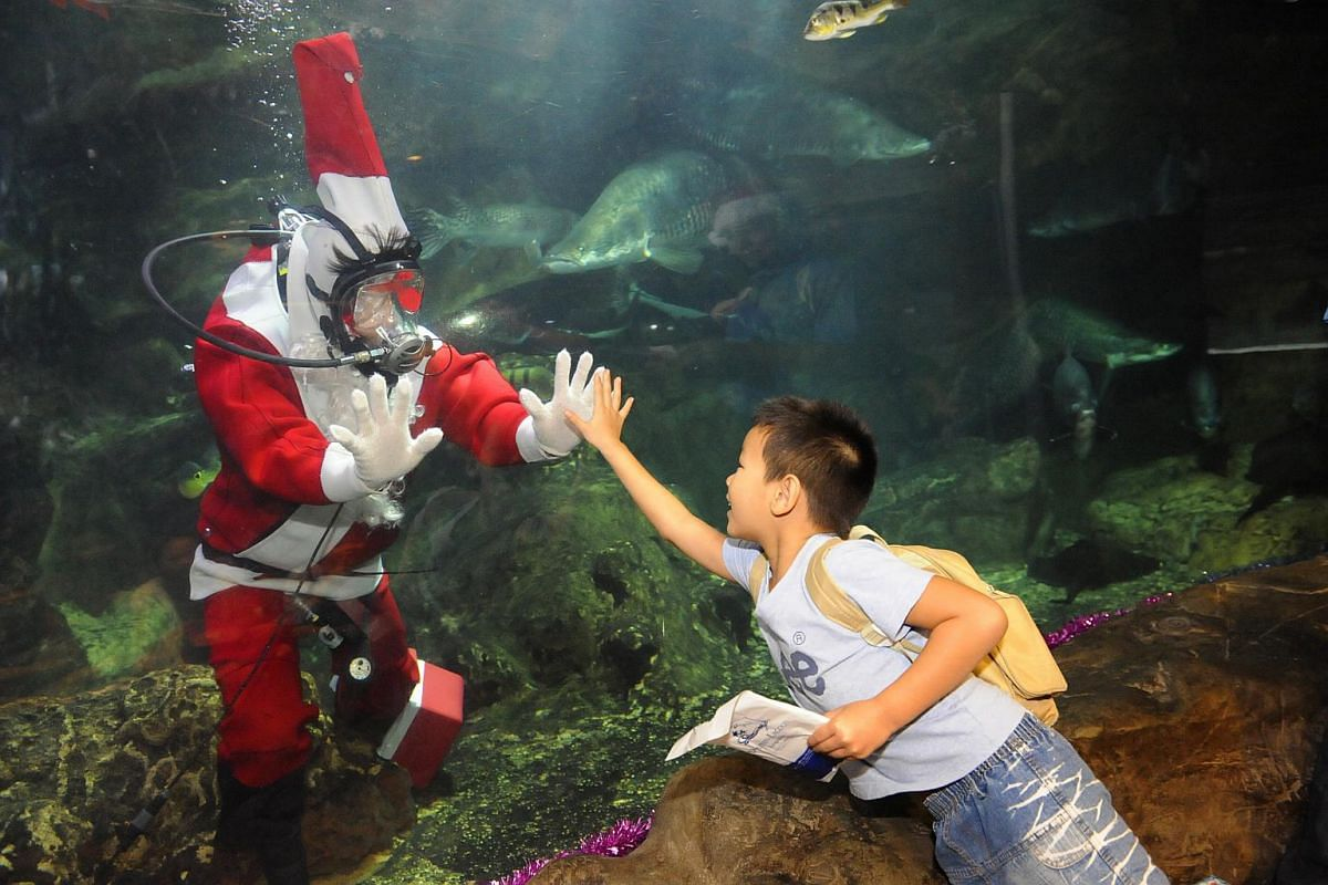 Visitor Liang Shi Cheng thanking an underwater Santa after receiving a Christmas gift.