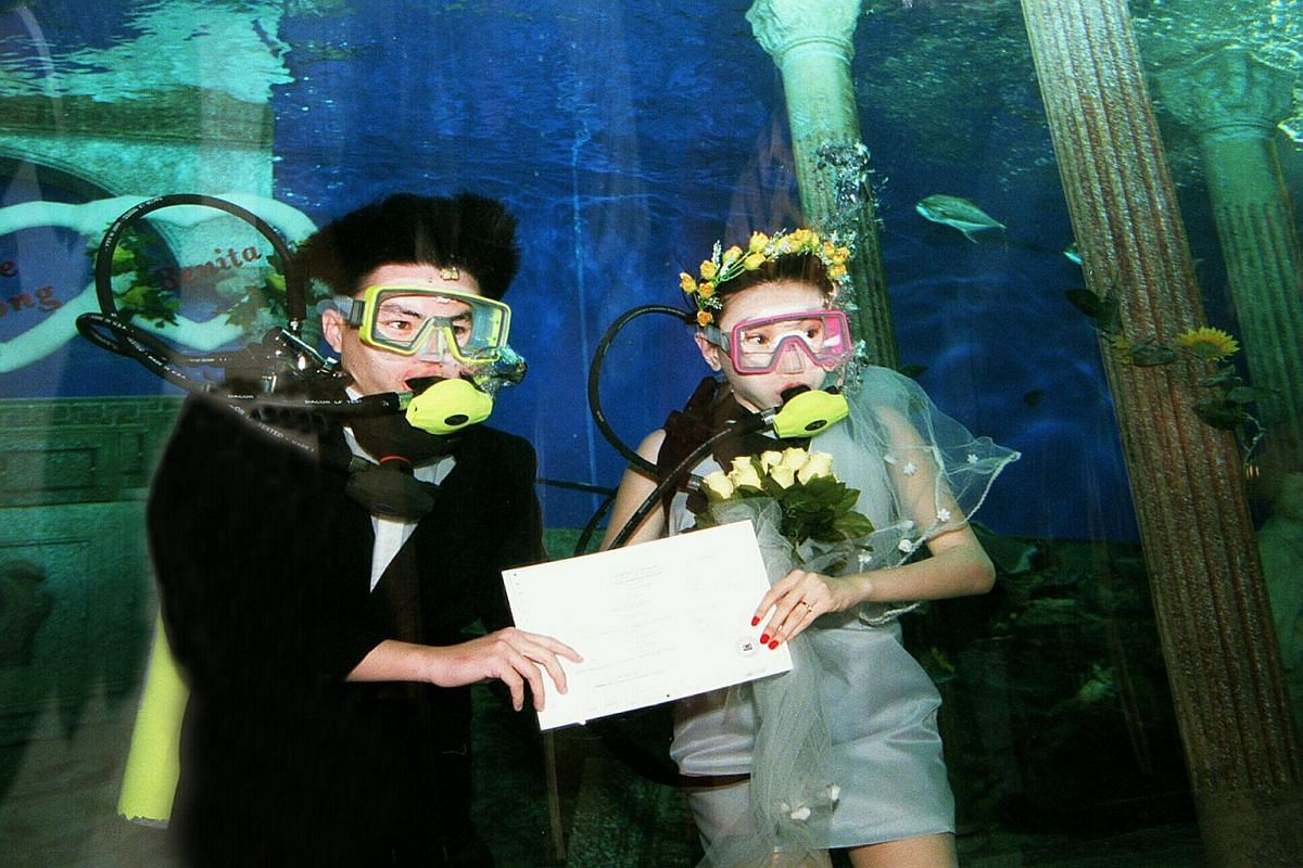 Showing their marriage certificate, Mr Kuan Chee Keong and Ms Benita Tan took the plunge by getting married several feet under the waters at Underwater World Singapore.