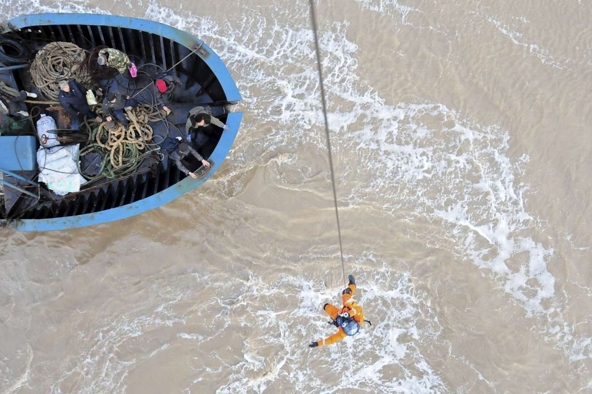 A rescue worker descends on a rope from a helicopter as he approaches a boat carrying fishermen trapped by bad weather, on the Bohai sea in Dongying, Shandong province on Nov 17, 2015.