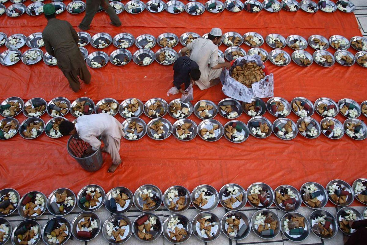 People serve food for Iftar, the time to break the fast, at a Mosque during the first day of the Muslim holy month of Ramadan, in Karachi, Pakistan on June 7, 2016.