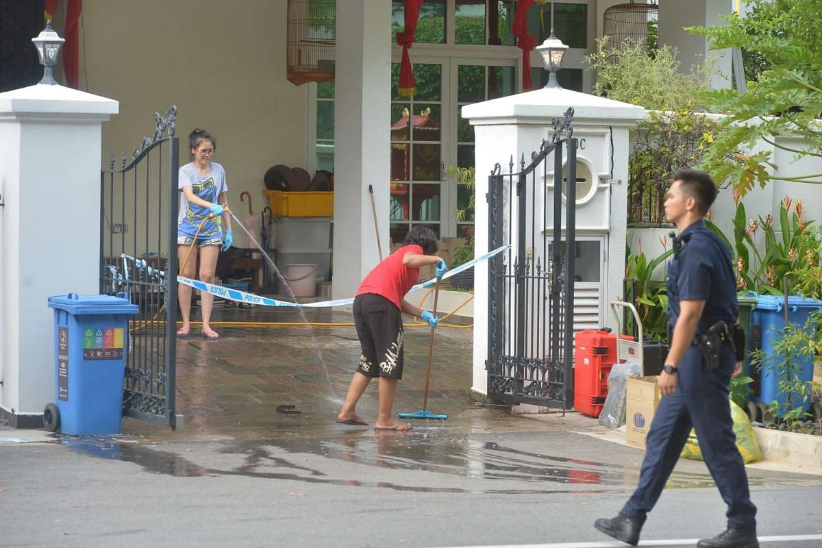 A woman and one of the maids (in red) wash blood stains off the porch floor at 50C Lorong H Telok Kurau on June 8, 2016, where a maid allegedly stabbed her employers.