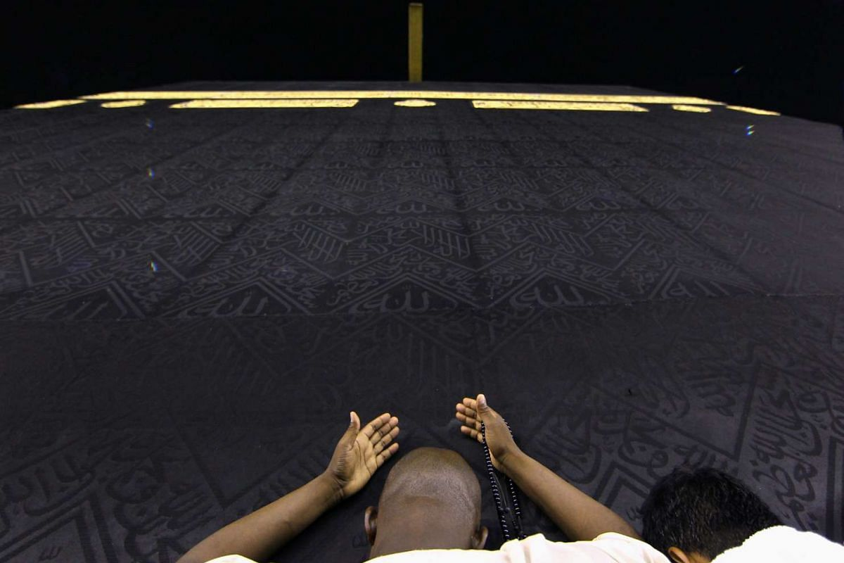Muslims pray and touch the holy Kaaba at the Grand Mosque during the holy fasting month of Ramadan in Mecca, Saudi Arabia on June 8, 2016.