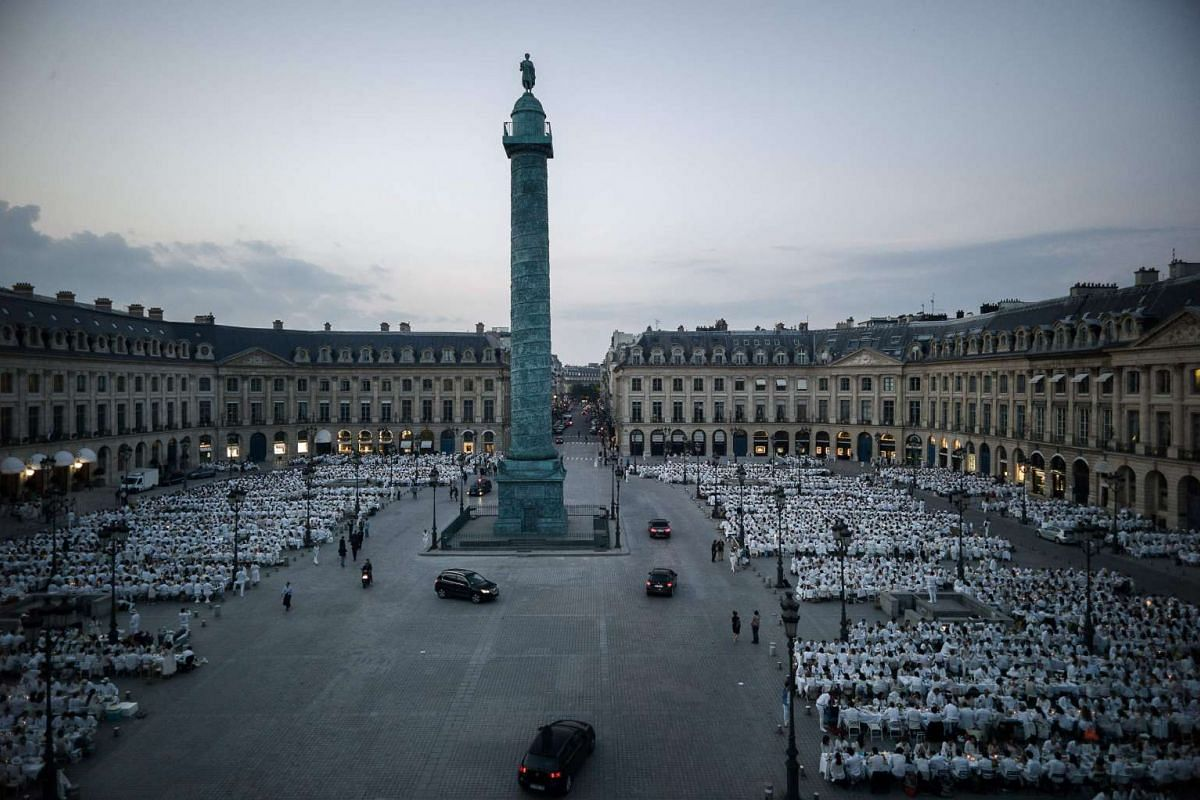 """People dressed in white gather for the """"Diner en Blanc"""" (Dinner in White) event at the place Vendome in Paris on June 8, 2016."""