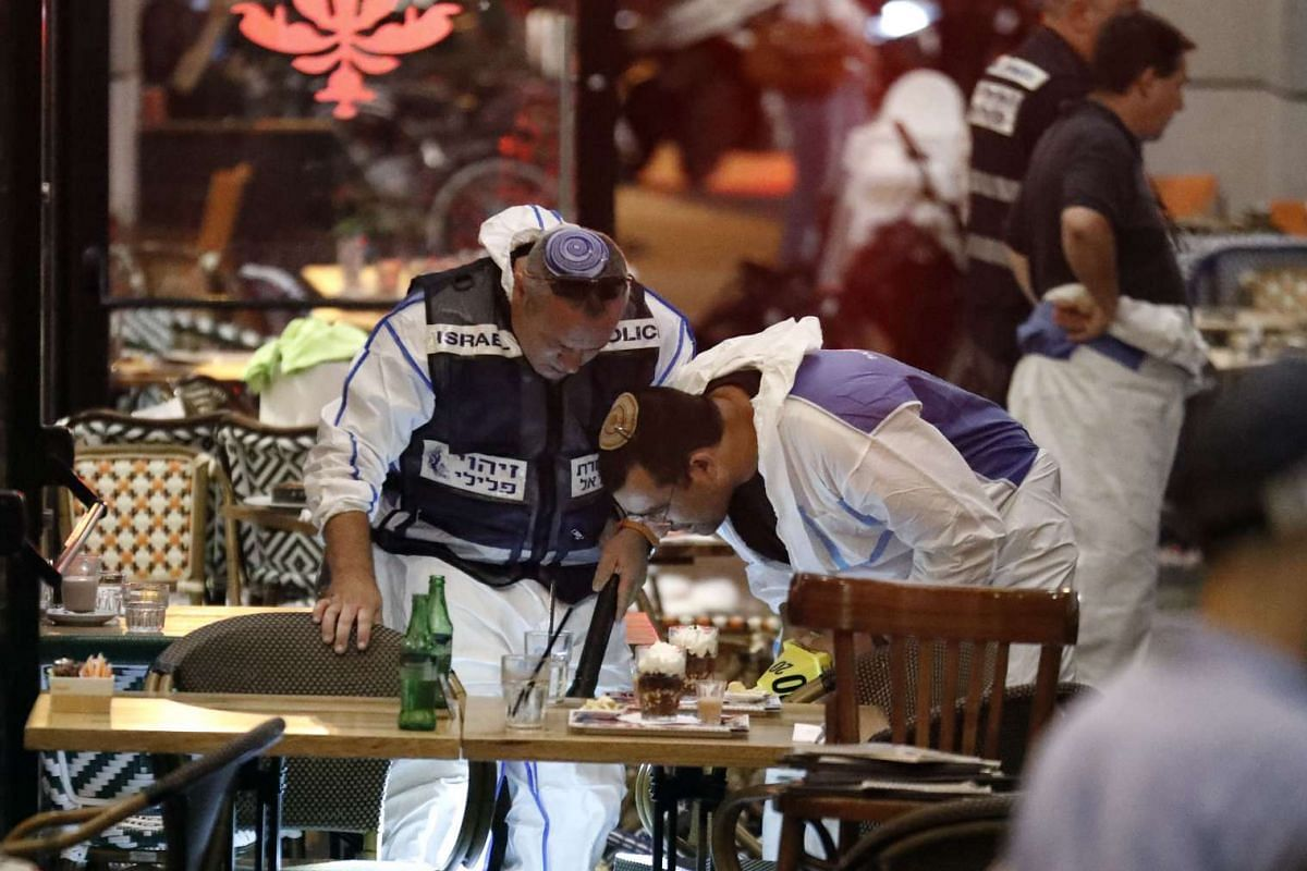 Israeli forensic police inspect a restaurant following a shooting attack at a shopping complex in the Mediterranean coastal city of Tel Aviv on June 8, 2016.