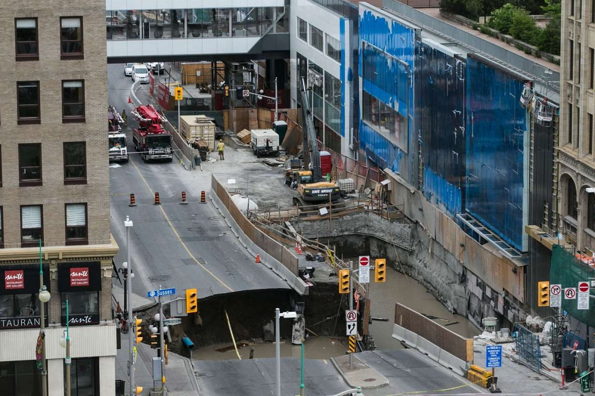 A large portion of Rideau Street in downtown Ottawa, Ontario is seen caved in, causing a massive sinkhole that knocked out power to the majority of the downtown area on June 8, 2016.