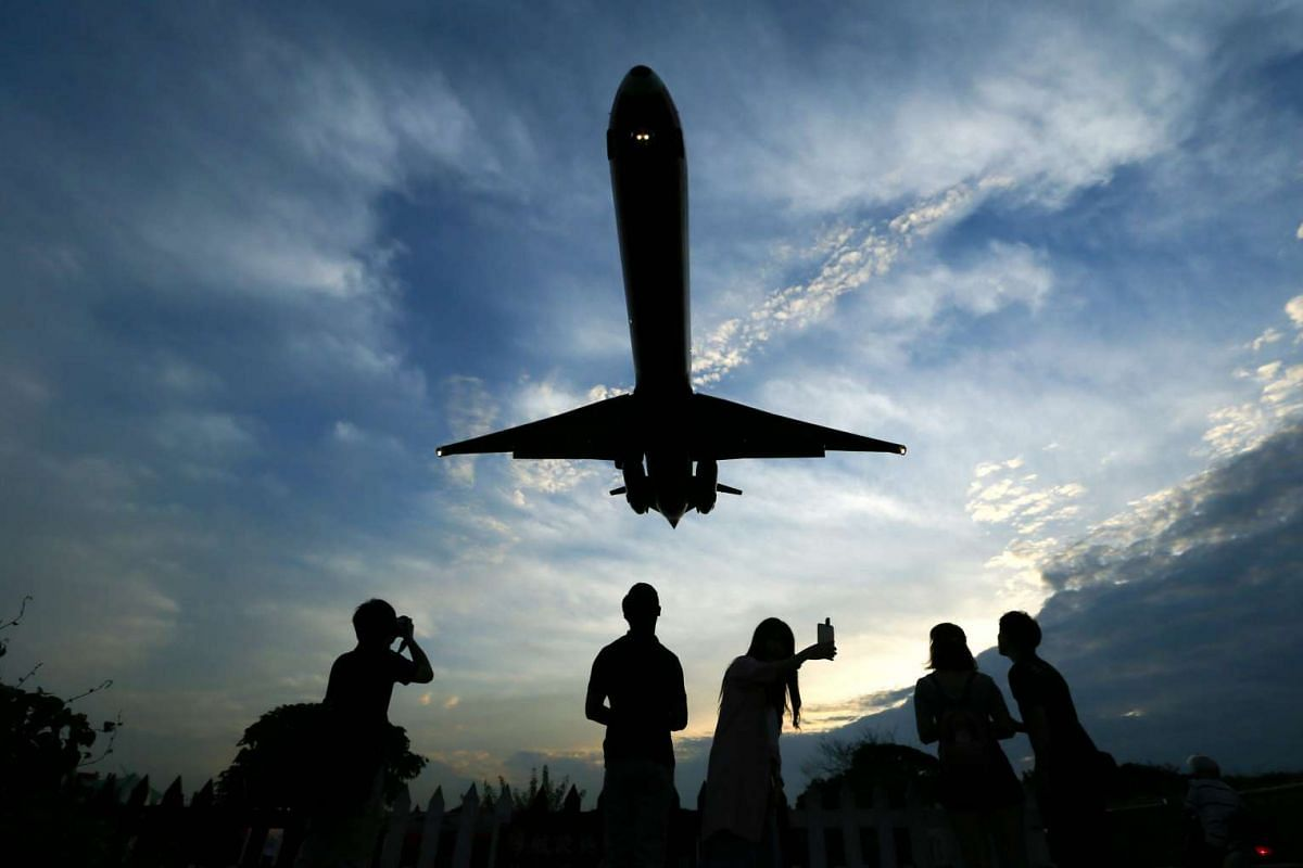 People photographing an airplane approaching to land at Songshan Airport in Taipei, Taiwan on June 8, 2016.
