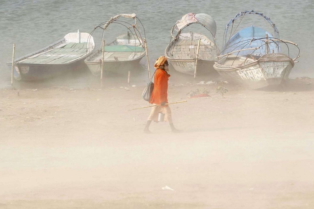 A Hindu holy man walks on the banks of the river Ganges during a dust storm in Allahabad, India on June 9, 2016.