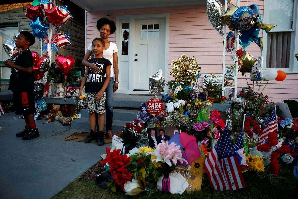 People pose for photos outside the childhood home of the late boxing champion Muhammad Ali in Louisville, Kentucky, on June 9, 2016.