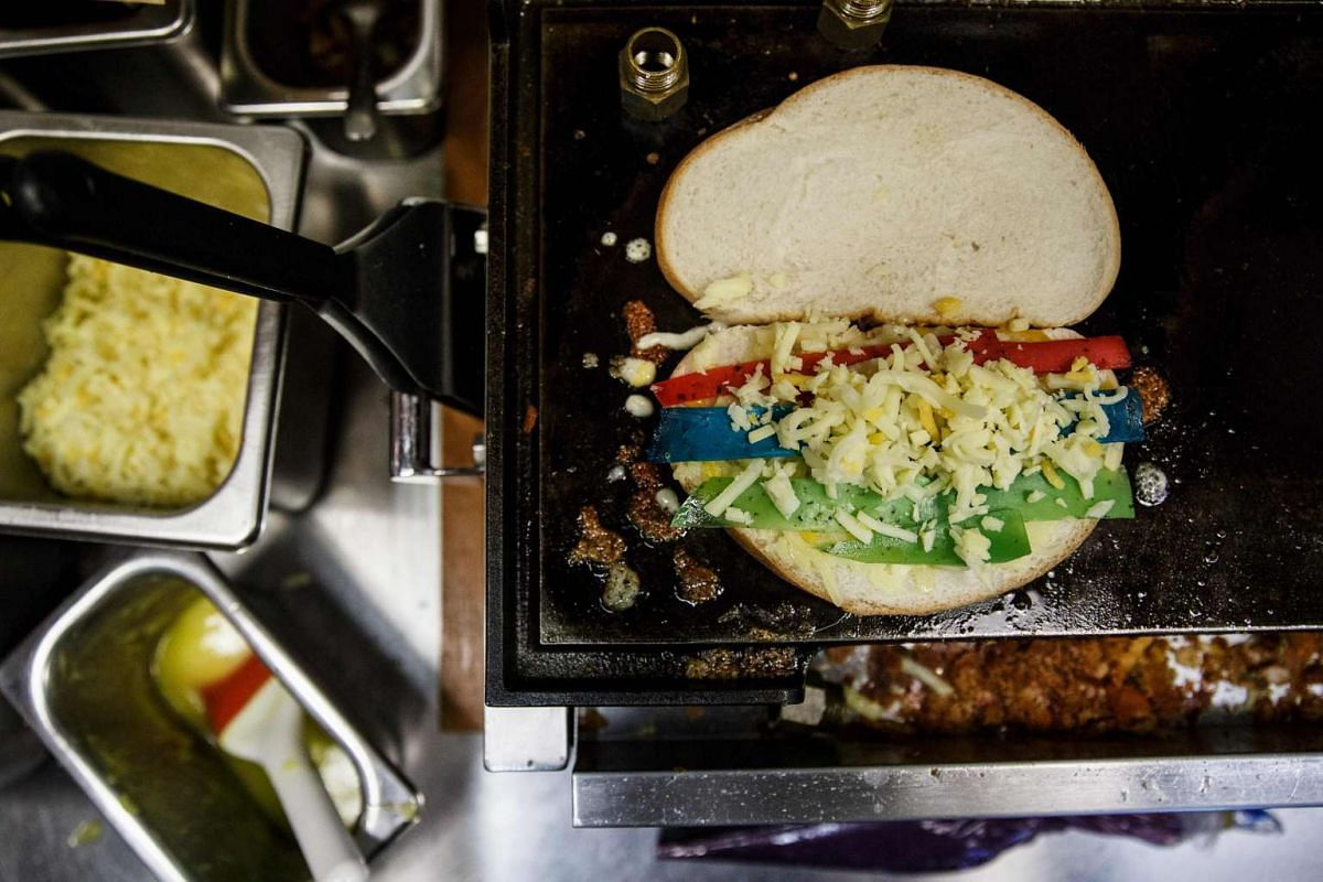 """A """"Rainbow Coloured Toast"""" cheese sandwich is placed upon a grill at Kala Toast in the Hong Kong suburb of Tsuen Wan, on June 8, 2016. The pint-sized shop uses imported coloured cheese, flavoured with lavender, basil and tomato, to create the rainbo"""