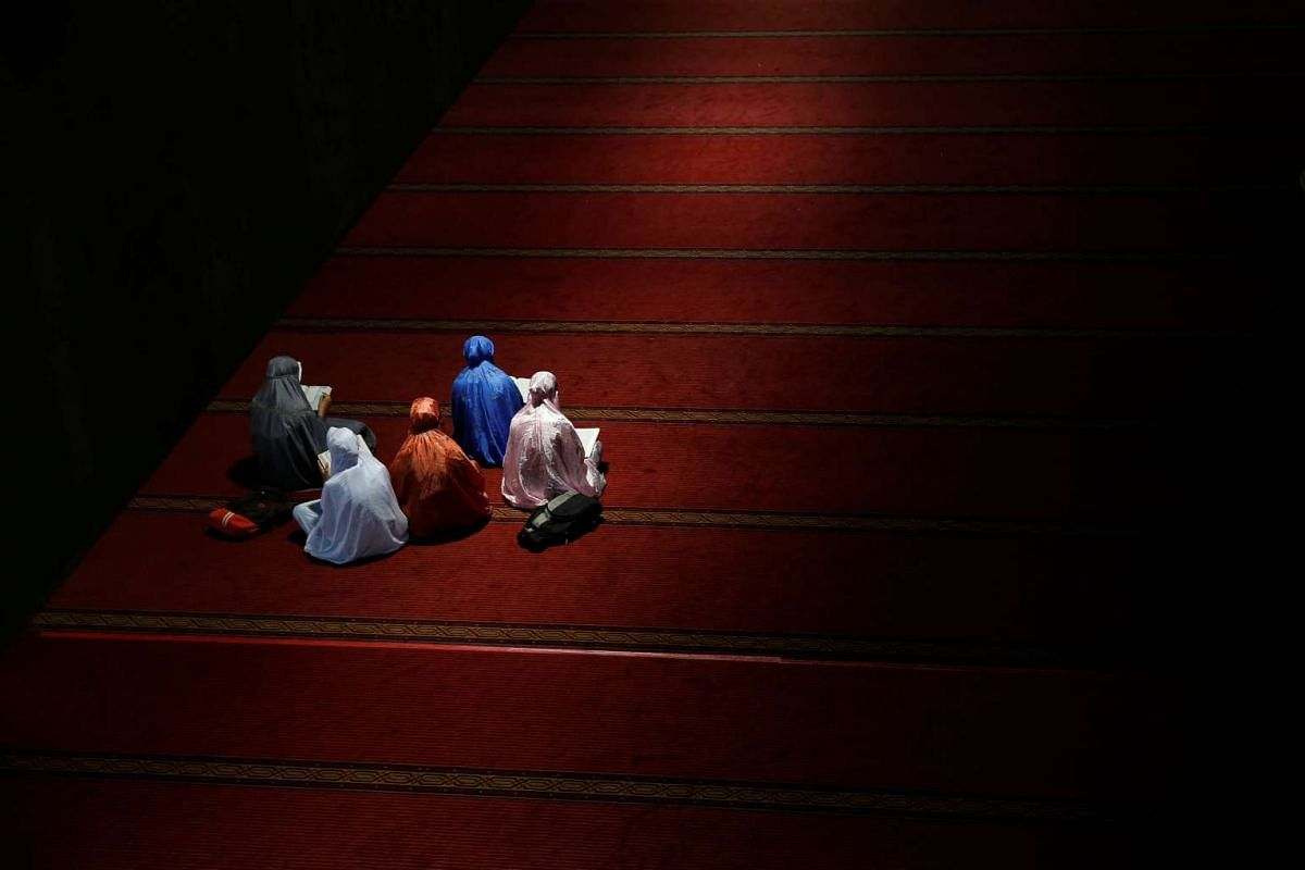 A group of youths read the Koran as they wait to break fast during the holy month of Ramadan inside Istiqlal mosque, in Jakarta, Indonesia, on June 9, 2016.