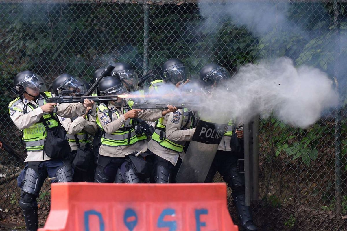 Riot police fire rubber bullets and tear gas grenades at students from the public Central University of Venezuela, who demonstrate in demand of the referendum on removing President Nicolas Maduro, on June 9, 2016.