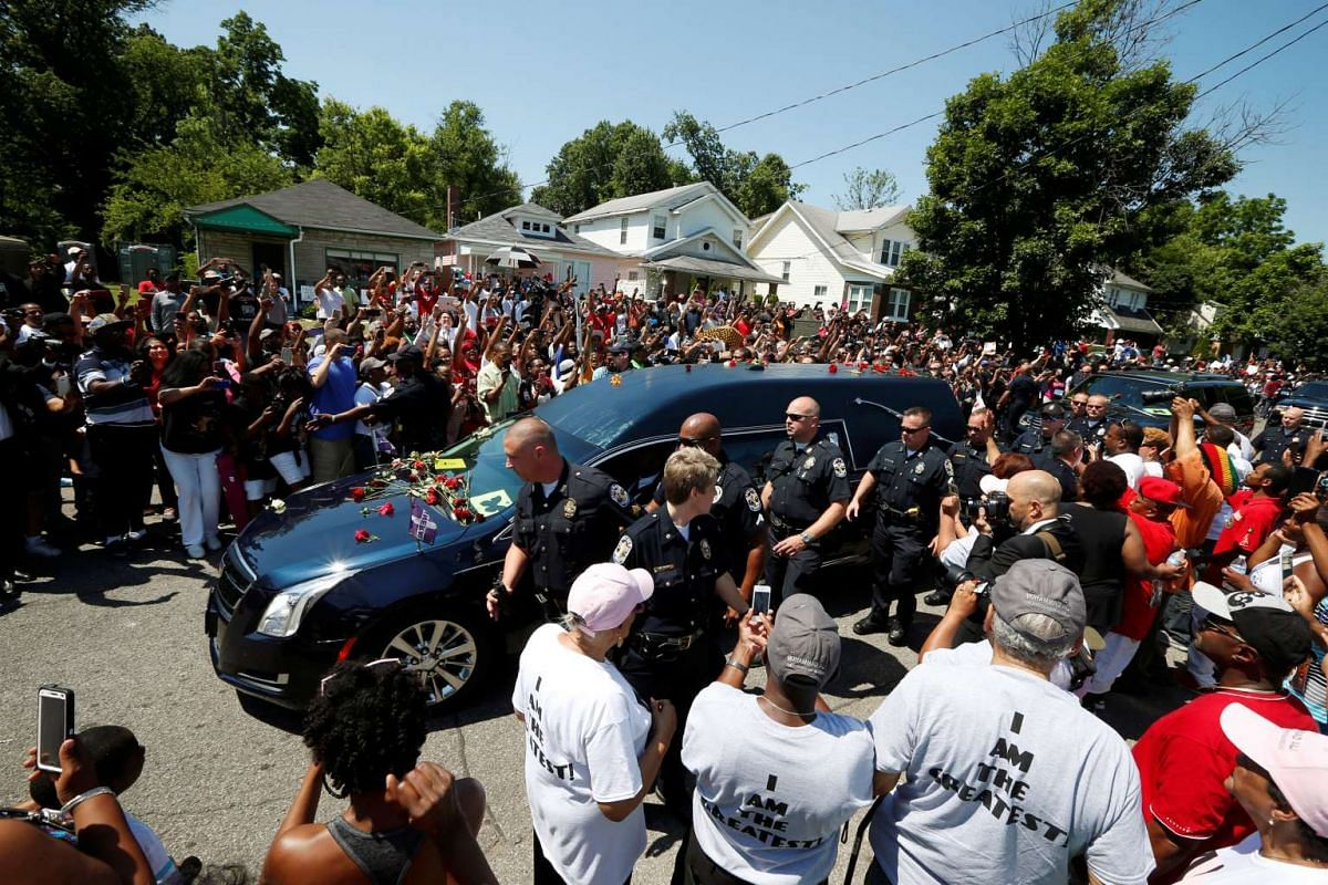 A hearse carrying the late boxing champion Muhammad Ali passes Ali's childhood home in Louisville, Kentucky.