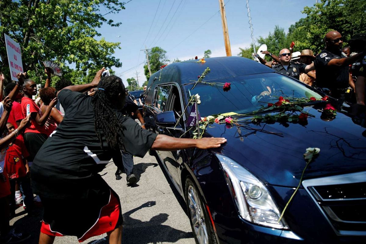 A man touches the hearse carrying the remains of Muhammad Ali during the funeral procession.
