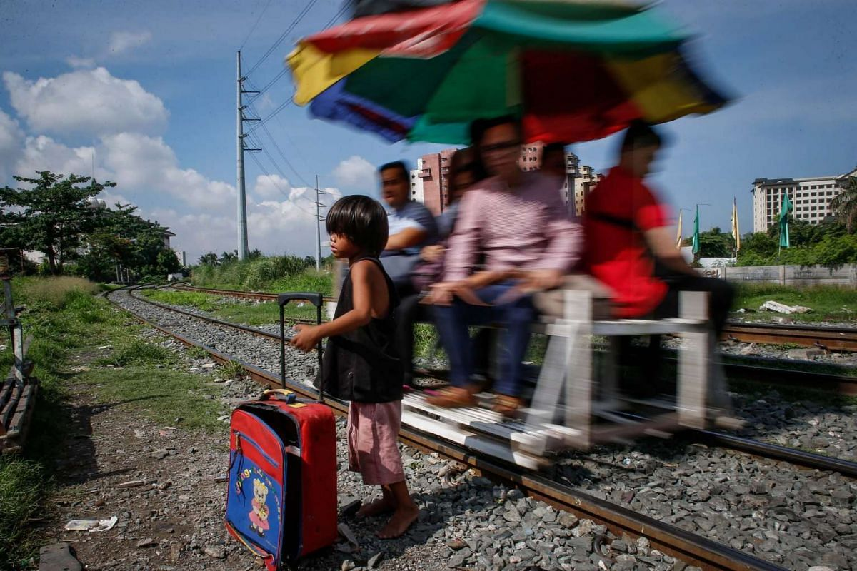 A Filipino child holds his bag as a makeshift railway trolley passes by during the opening of classes in Manila, Philippines, on June 13, 2016.