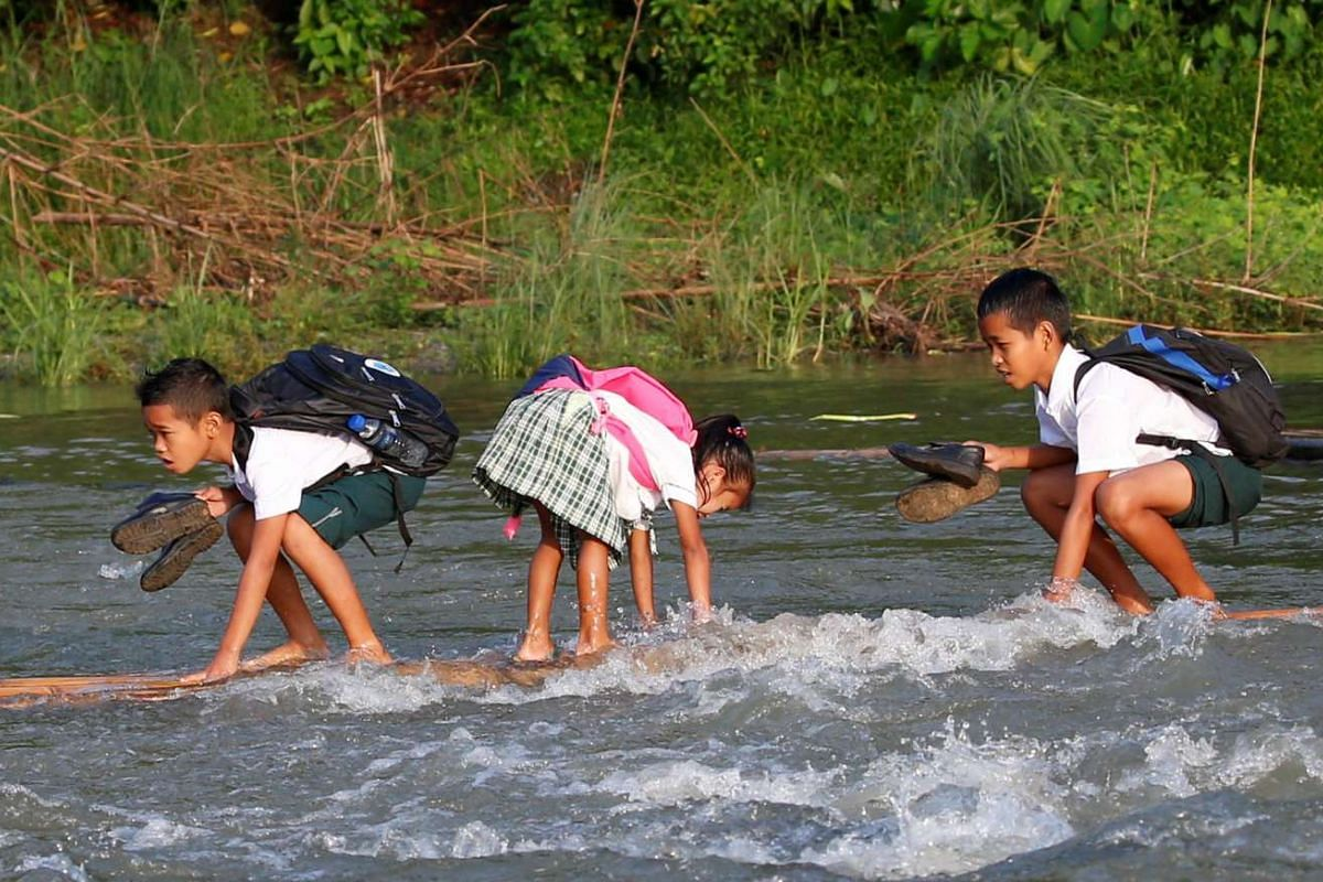 Schoolchildren ride on a makeshift raft to attend the opening of classes at a remote Casili Elementary School in Montalban, Rizal, northeast of Manila, Philippines, on June 13, 2016.