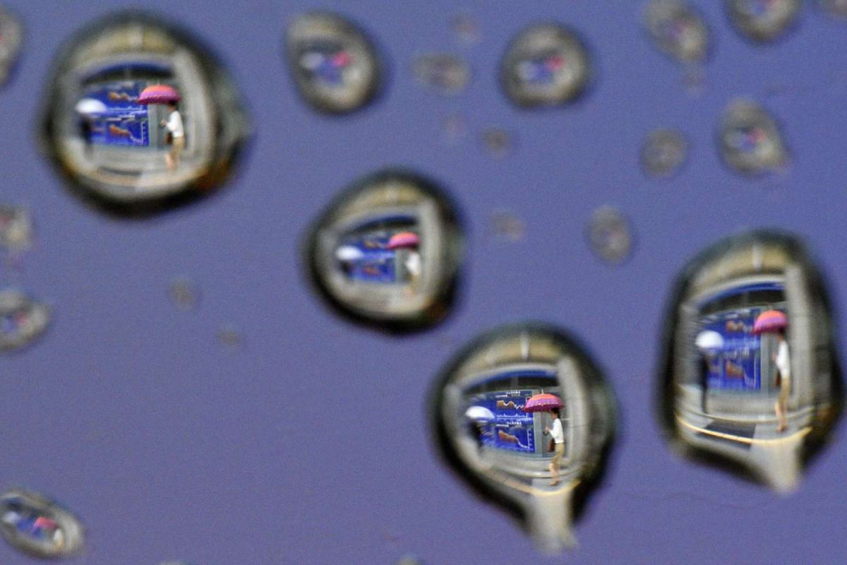 An image rotated 180 degrees shows raindrops on a car window reflecting pedestrians walking past a stock market indicator board in Tokyo, Japan, on June 13, 2016.