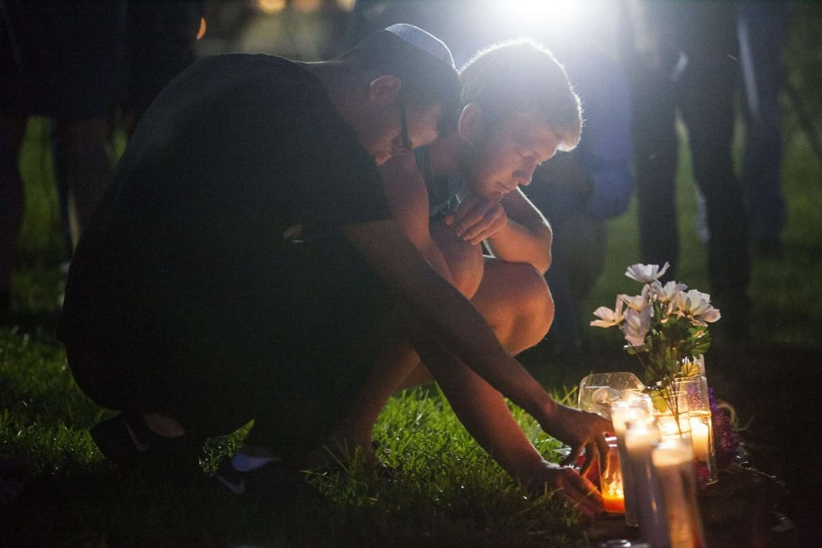 Two men light candles during a vigil to honour the victims of a mass shooting at a nightclub, at Eola Lake Park in Orlando, Florida, on June 12, 2016.