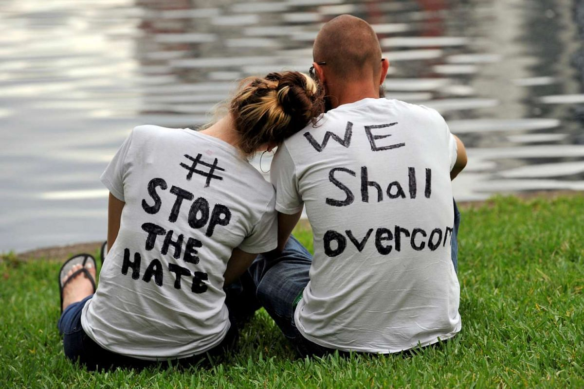 Orlando residents Arissa Suarez (left) and Malcom Crawson attend a vigil at Lake Eola Park for victims of the Orlando shooting.