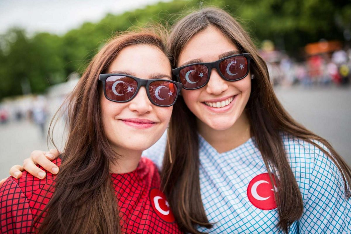 "Deniz (left) and Gozde wear Turkey jerseys on the ""Fanmeile"" (Fan mile) in front of the Brandenburg Gate where the Uefa Euro 2016 soccer match between Germany and Ukraine will be broadcasted live later on the same day, in Berlin, Germany on June 12,"