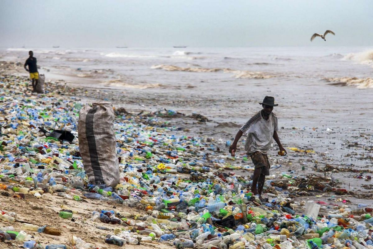 A Ghanaian collects recyclable material at the polluted Korle Gono beach, that is covered in plastic bottles and other items washed ashore, following weeks of heavy flooding in Accra, Ghana, on June 12, 2016.