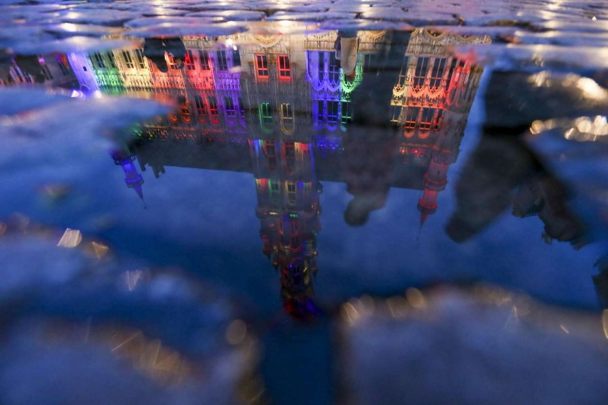The City Hall and Grand Place of Brussels illuminated in rainbow colours for the victims of a mass shooting in Orlando, are reflected in a puddle in Brussels, Belgium, on June 13, 2016.