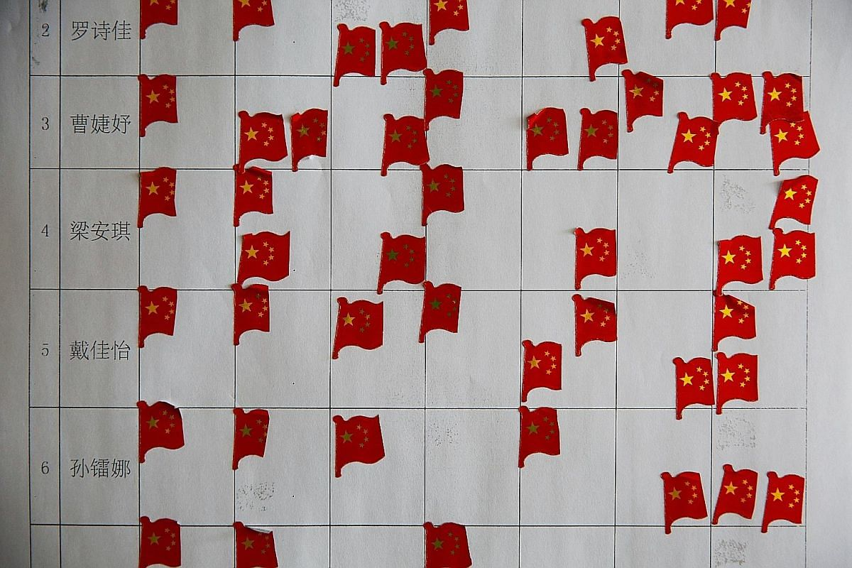 (Left) Stickers in the shape of Chinese flags marking an achievement board on the wall of a dormitory at Beijing's Shichahai sports school. (Above, left) A student donning her helmet during fencing training at the school. Its famous alumni include Ol