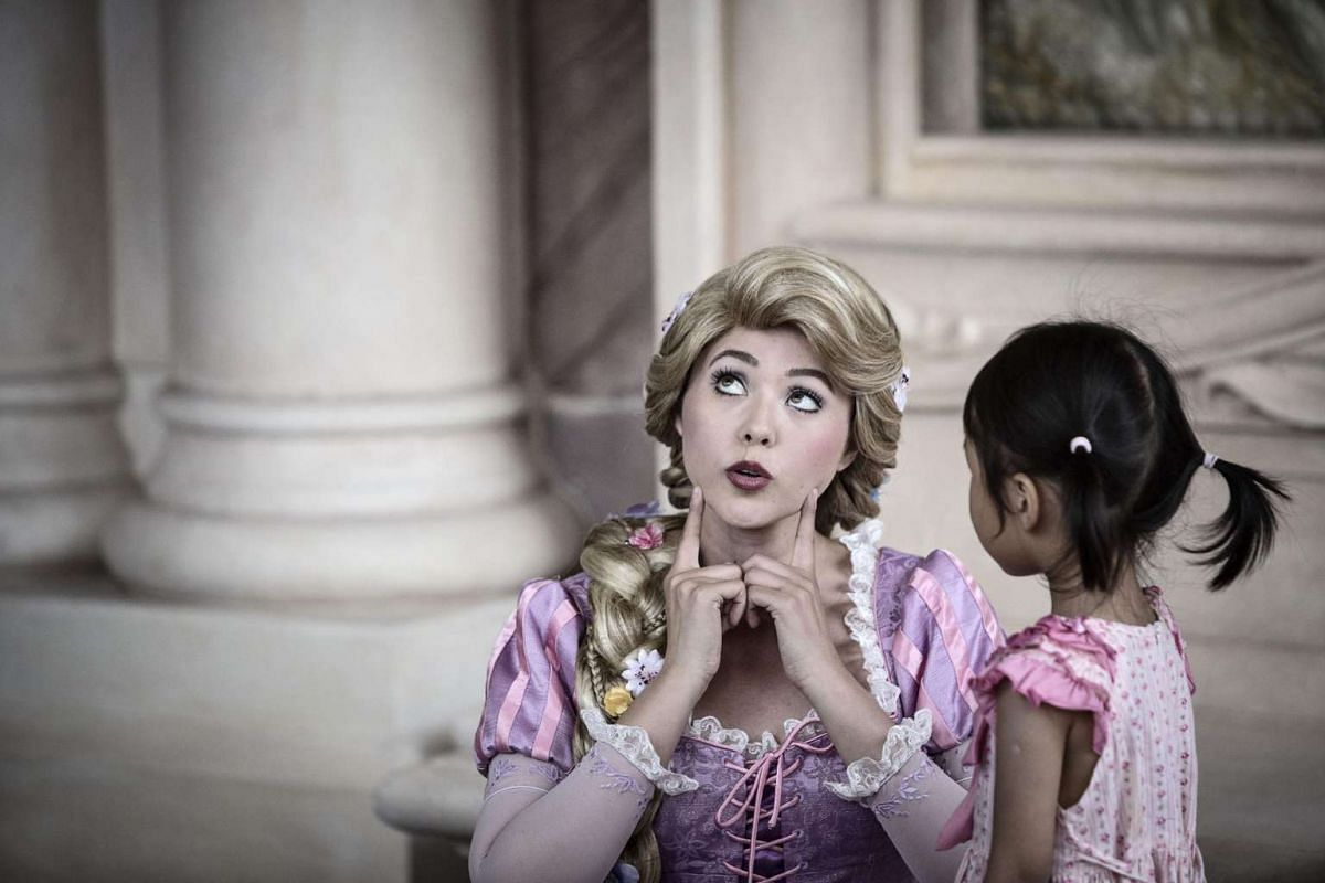 An actress dressed as Rapunzel speaks with a young girl at Walt Disney Co.'s Shanghai Disneyland theme park during a trial run ahead of its official opening on June 8, 2016.