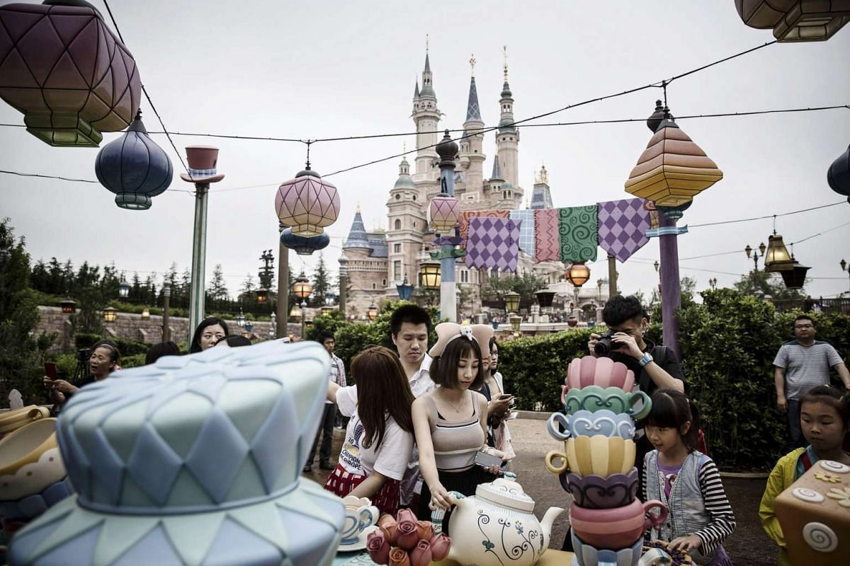Visitors walk through the Mad Hatter's Tea Party area of the Alice in Wonderland Maze at Walt Disney Co.'s Shanghai Disneyland theme park on June 8, 2016.