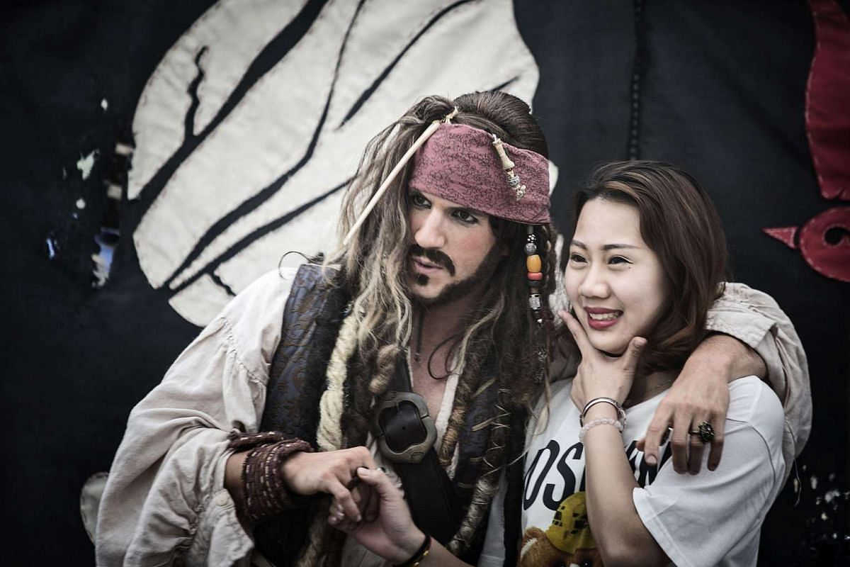 """A visitor poses with an actor dressed as Captain Jack Sparrow from """"Pirates of the Caribbean"""" at Walt Disney Co.'s Shanghai Disneyland theme park on June 8, 2016."""