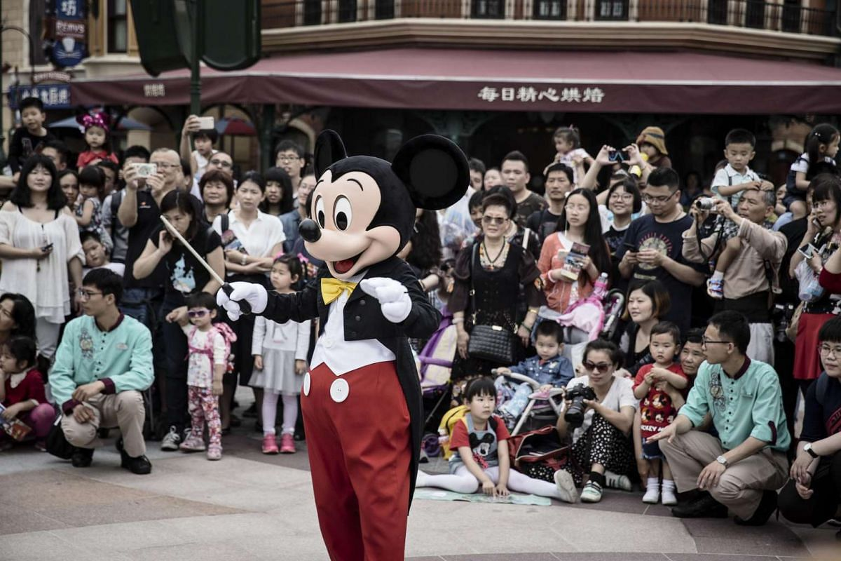 An actor dressed as Mickey Mouse raises a baton as a marching band and audience members look on at Walt Disney Co.'s Shanghai Disneyland theme park on June 8, 2016.