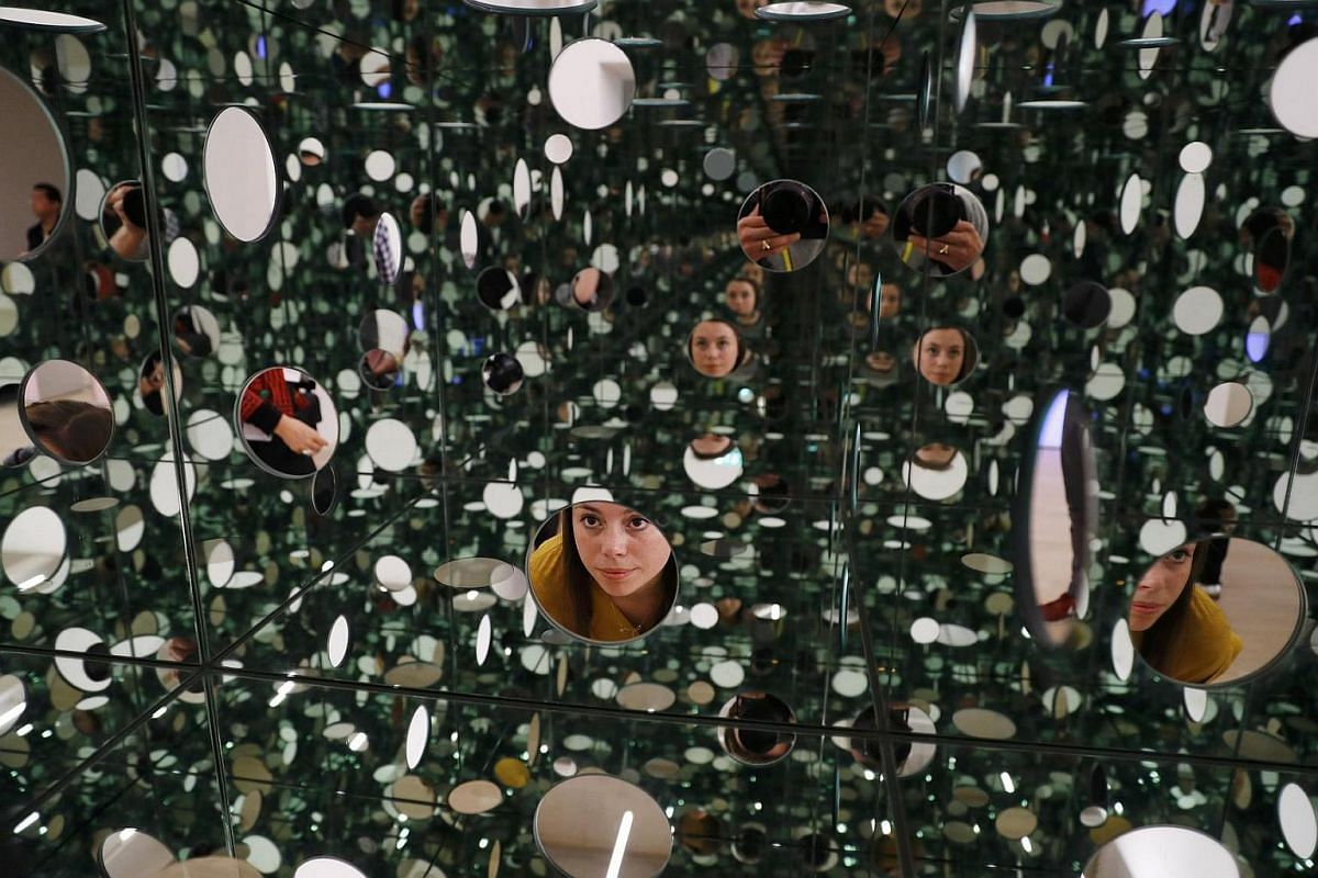 """A museum assistant posing with """"Mirror and glass"""" by Yayoi Kusama during the unveiling of the New Tate Modern in London on June 14."""