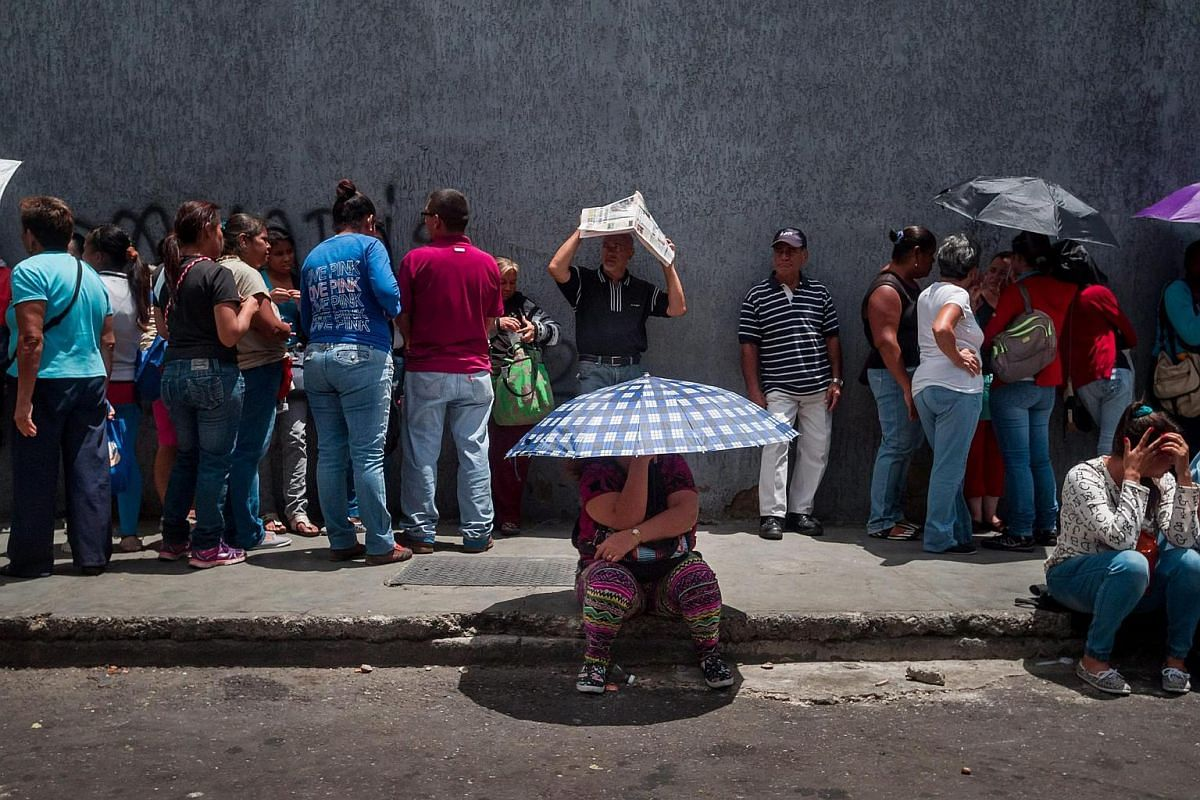 People lining up to get food at a distribution point during a protest in the district of Catia in Caracas, Venezuela, on June 14.