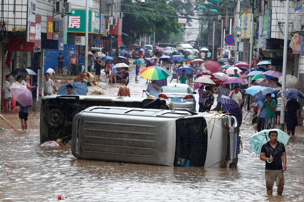 Automobiles are seen overturned on a flooded street in Liuzhou, China, on June 14.