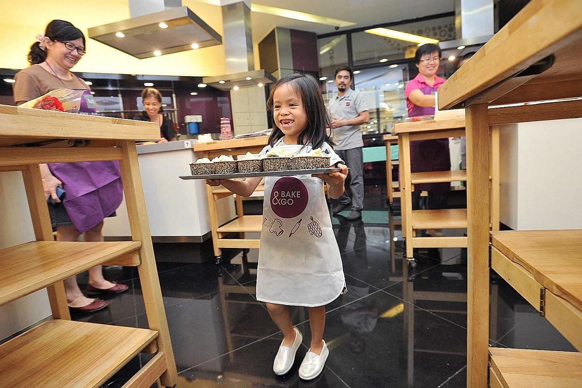 Faith carrying a tray of cupcakes which she and her mother baked at a Mother's Day baking event organised by the Haemophilia Society of Singapore (HSS) on May 2. Besides providing financial help and support for people with haemophilia and their famil