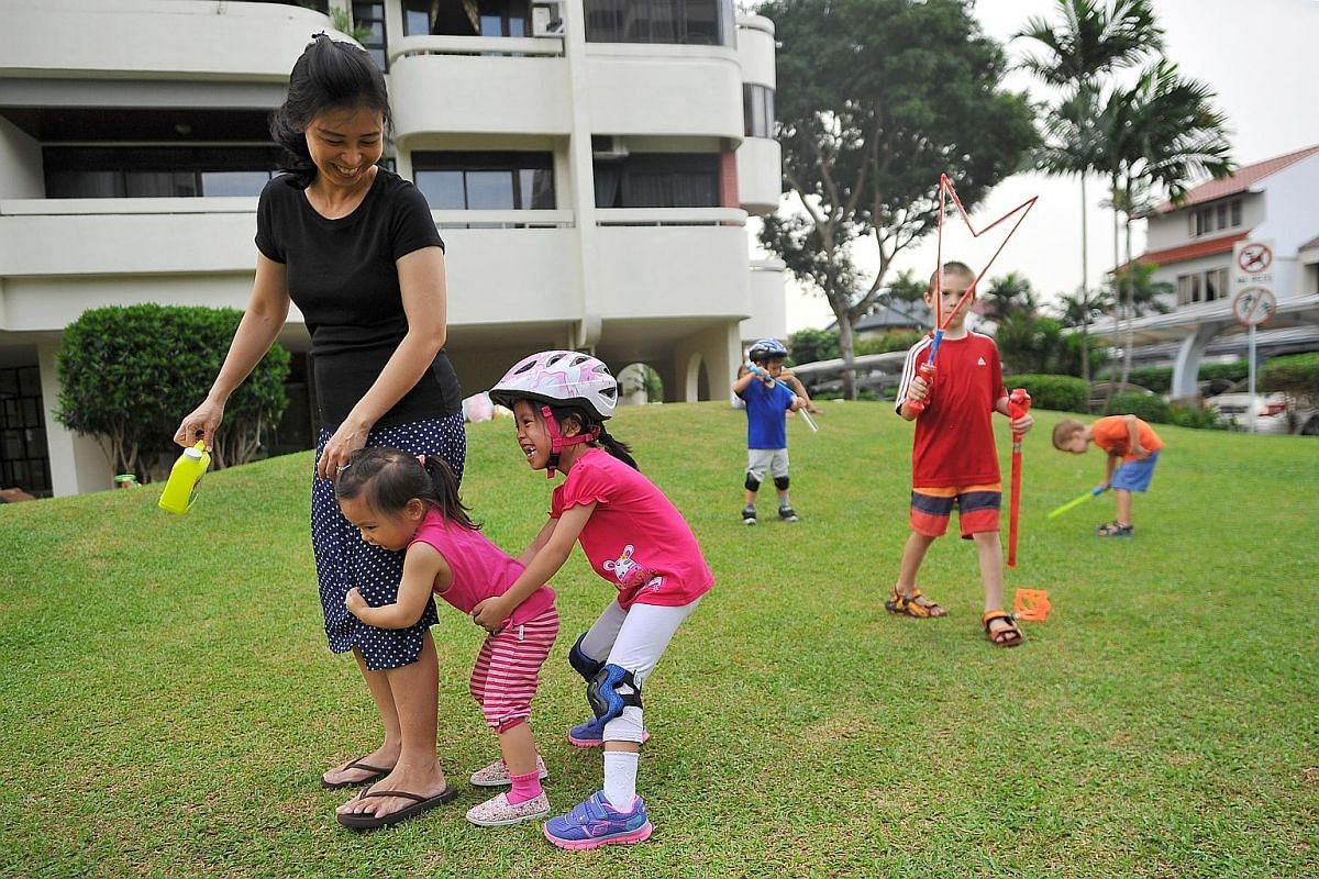 """Swimming instructor Koh Bee Bee, 43, throws Faith into the air at a swimming pool. This is Faith and James' reward after a swimming lesson - it is like a """"helicopter ride"""" for them, says Ms Koh. Exercise - especially swimming, which has low impact -"""