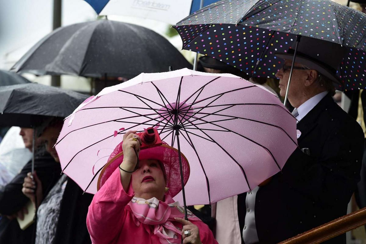 Racegoers at Britain's Royal Ascot use umbrellas to shield themselves from the rain on June 15, 2016.