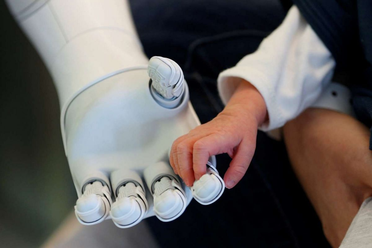 """New recruit """"Pepper"""" the robot, a humanoid robot designed to welcome and take care of visitors and patients, holds the hand of a new born baby at AZ Damiaan hospital in Ostend, Belgium on June 16, 2016."""